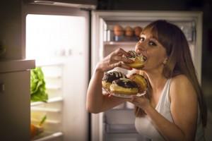 Een vrouw bij de koelkast die donuts eet maar graag wil afvallen met hypnose via de virtuele maagband